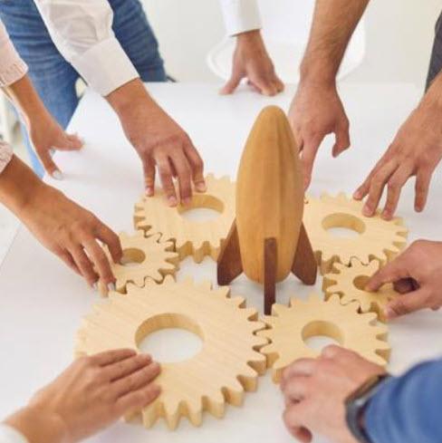 teamwork model, showing hands touching gears surrounding a rocket ship
